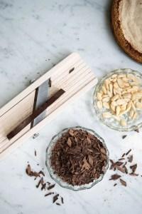 Den Bøhmiske nøddelagkage er pyntet med revet chokolade og ristede mandler. På billedet kan man se at jeg river chokoladen på min mandolin. Der er også en skål med ristede mandler og en lille stykke af kagen så man kan se hvordan den ser ud før den bliver lagt sammen som lagkage