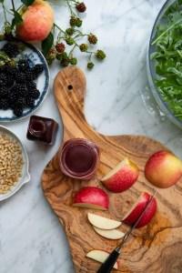 Brombæreddiken på køkkenbordet omgivet af brombær, salat og friske brombær