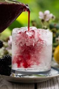 Brombærsirup hældes ud over en Bramble drink