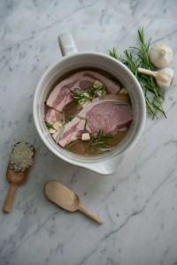 Her er koteletterne i kryddermarineringen omgivet af rosmarin, hvidløg salt og peber