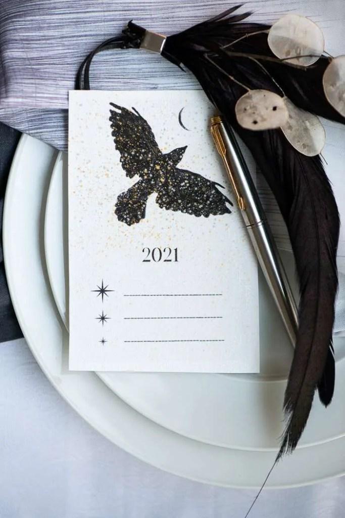 En vinterfugl flyver mod månen. Der er dækket op med nytårsfortsætter og hvide tallerkner