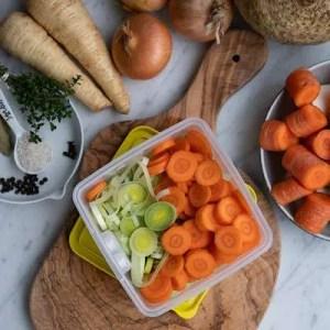 Grøntsager til hønsekødssuppe. I midten boksen med suppefyld . rundt om andre grøntsager hele og i grove stykker.