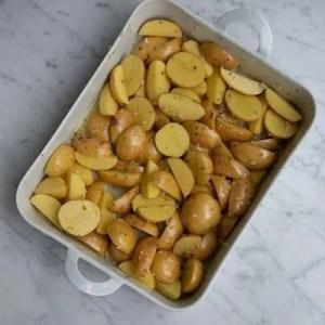 Kartoflerne er fordelt i det ildfaste fad og er blevet vendt rundt i marinaden
