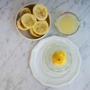 Her kan man se de pressede citroner og hvordan der måles ca 2 dl saft op