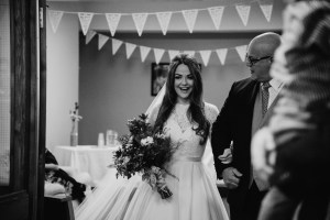 Bride smiles and walks into church with her dad