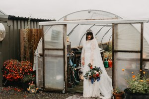 Bride standing in a greenhouse with a flower bouquet