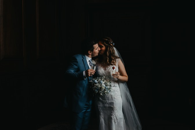 A bride and groom kisses as they have a drink