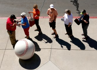 People wait to have their bags checked by security as they enter the ballpark before a spring training baseball game between the Seattle Mariners and the Kansas City Royals Wednesday, March 9, 2016, in Peoria, Ariz. (AP Photo/Charlie Riedel)