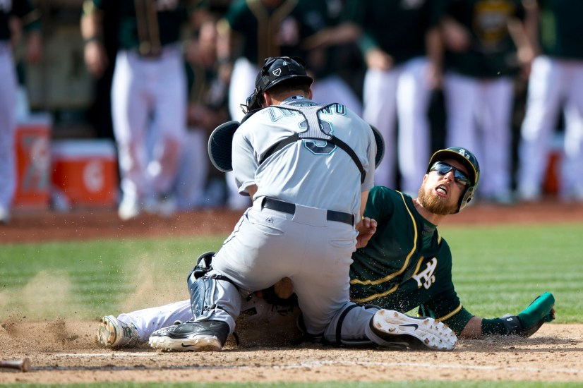 OAKLAND, CA - APRIL 11: Ben Zobrist #18 of the Oakland Athletics is tagged out at home plate by Mike Zunino #3 of the Seattle Mariners during the tenth inning at O.co Coliseum on April 11, 2015 in Oakland, California. The Seattle Mariners defeated the Oakland Athletics 5-4 in 11 innings. (Photo by Jason O. Watson/Getty Images)