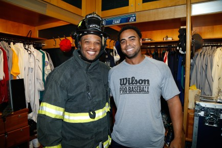 Robinson Canó tries on Nelson's new gear from Seattle Fire Department.