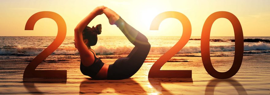 Silhouette of healthy girl doing Yoga Bow pose on tropical beach with sunset sky background, woman practicing yoga as a part of the Number 2020 sign.