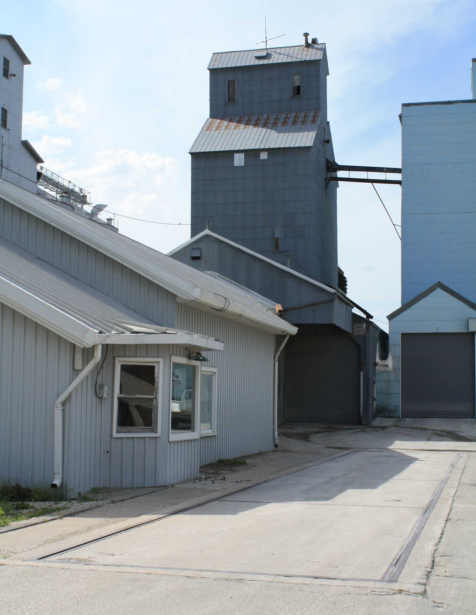 The former Farmers Co-op grain elevator office and scale, used until moving to the new location across the street in 2002.  The scale dial hung in the window and was used until the early/mid 1980's when it was replaced with a digital readout and printer system.  (Click photo to enlarge.).