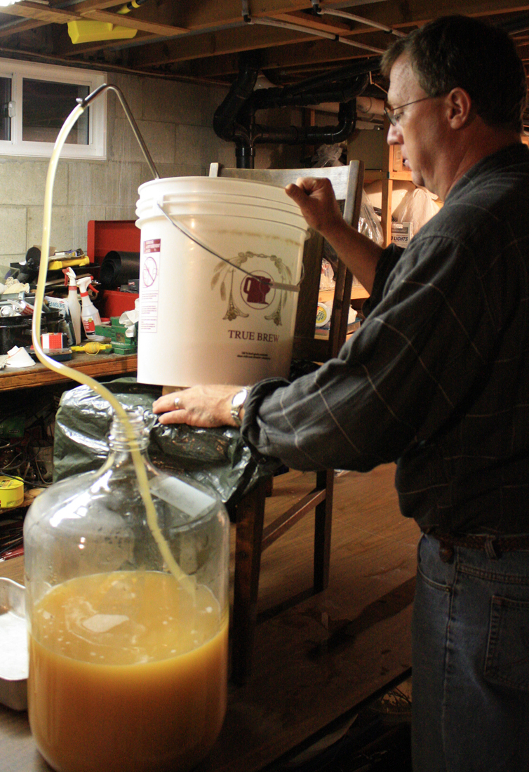 Scott's making sure the tilt of the bucket prevents the sediment from going into the carboy.  (Click photo to enlarge.)