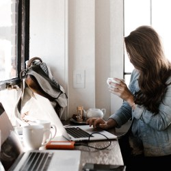 girl with busy desk space and coffee, self-sabotaging habits