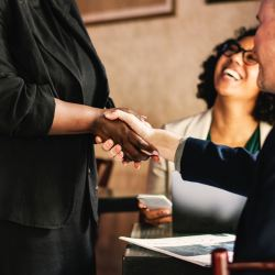 woman and man shaking hands, growing success