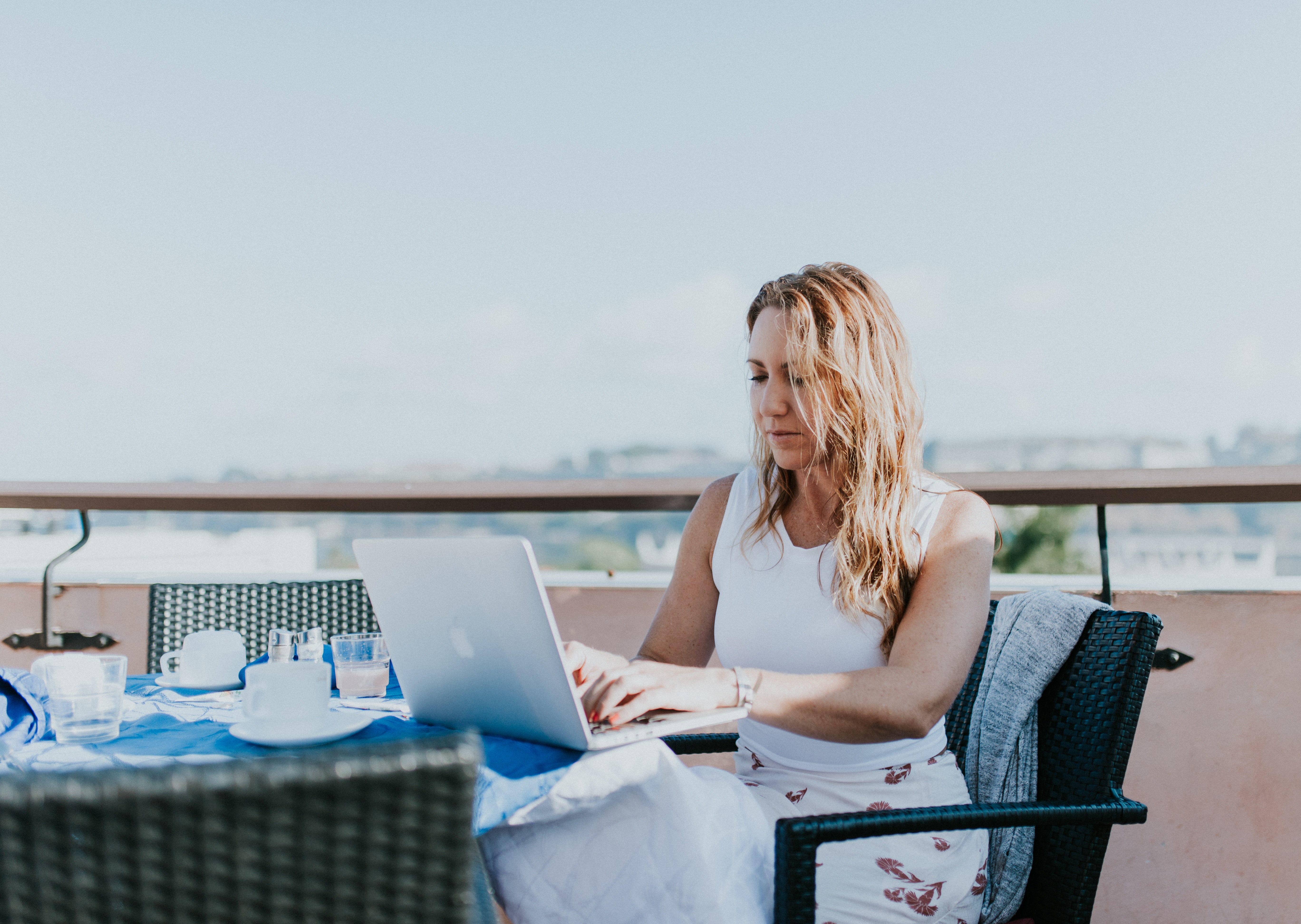 tips for working remotely, digital nomad, girl working at table
