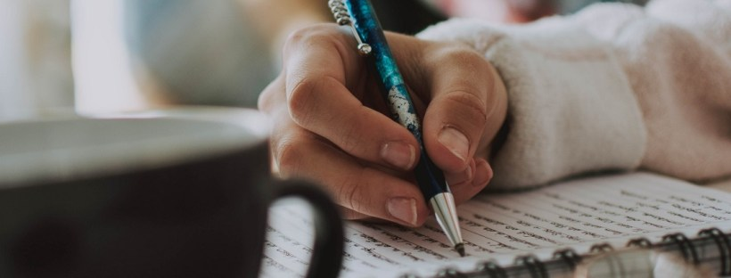 person writing in notebook, ways to write more this year