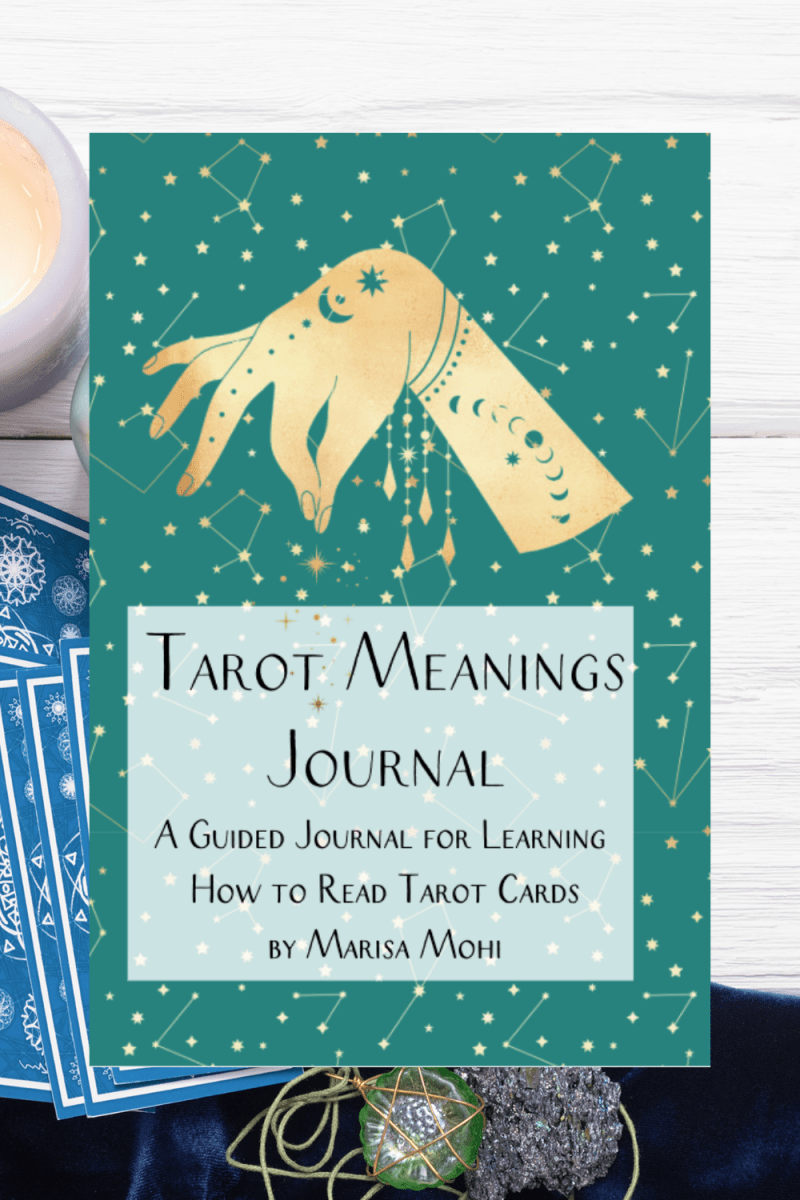 tarot cards laid out with a pendant with the over of the tarot card meanings journal over it