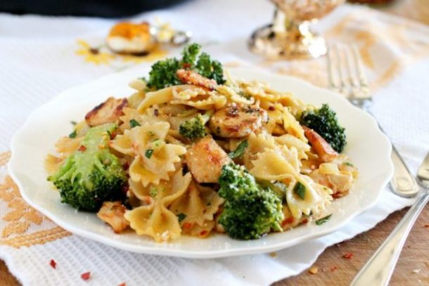 Broccoli and Chicken with pasta served on a white plate.