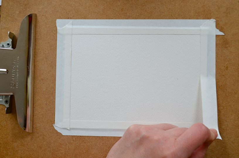 "Step 1: Tape down your watercolor paper. I place artist tape on a piece of paper leaving about 1/2"" white border around the paper. I use a clipboard or a masonite board to paint on. This will help it to dry flat once you're done, especially if the paper is lighter weight (140 lb or lighter). Press down firmly on the tape to make sure paint won't seep through."