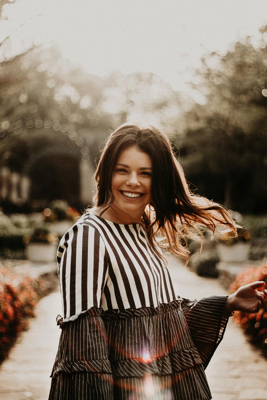girl flipping her hair in botanical gardens