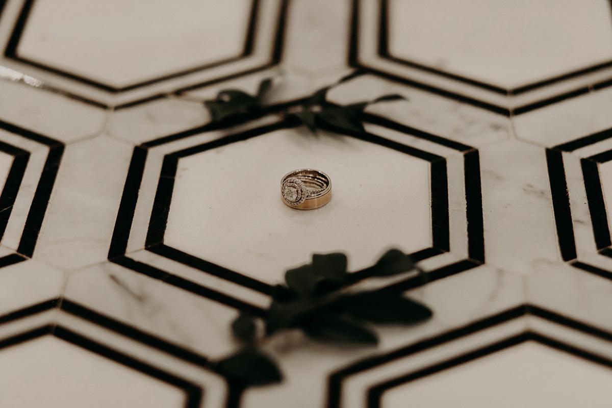 Wedding rings detail photo on marble floor