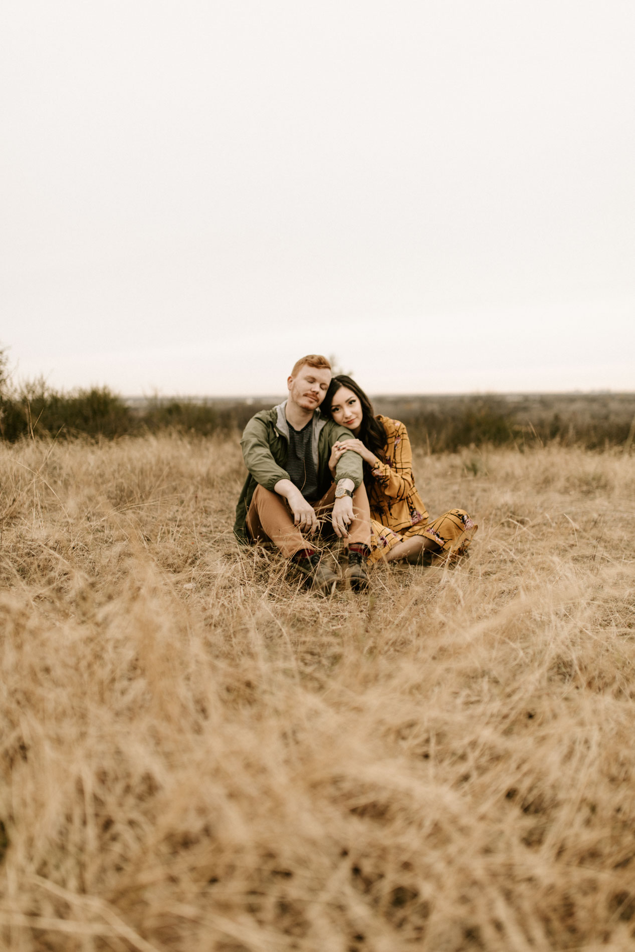couple sitting in field in Fort Worth