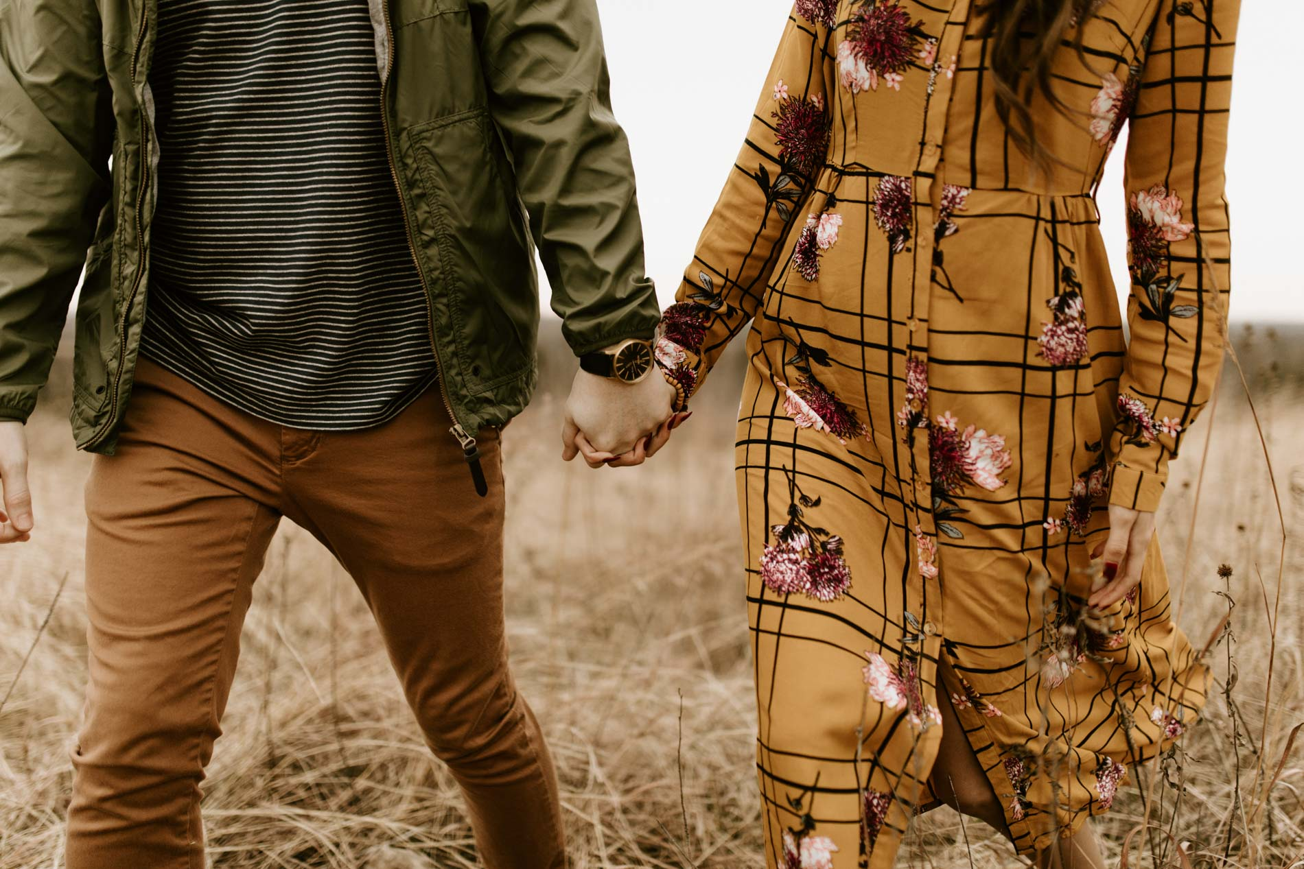 couple holding hands and walking in a field