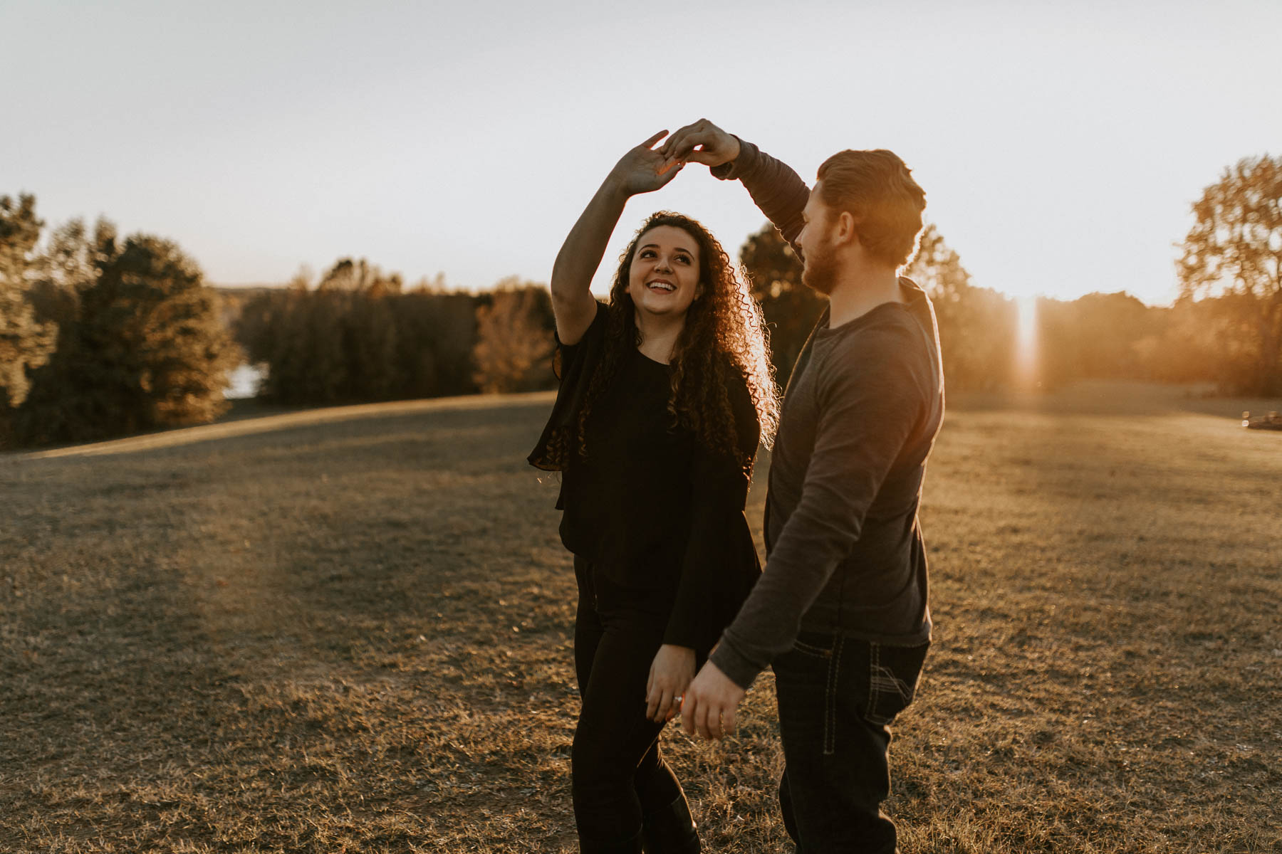 couple dancing and being playful in a field