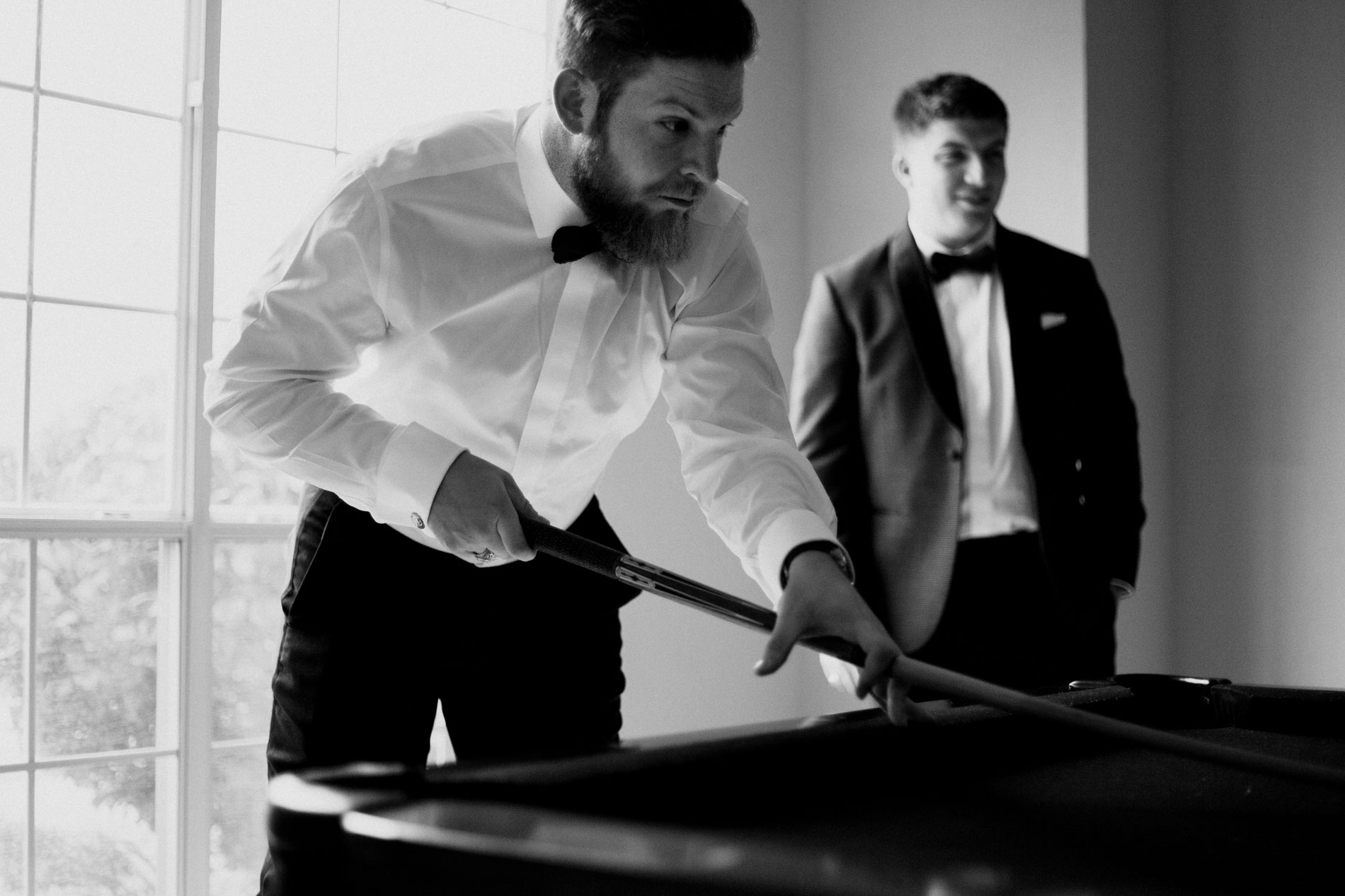 groomsmen playing pool before wedding ceremony