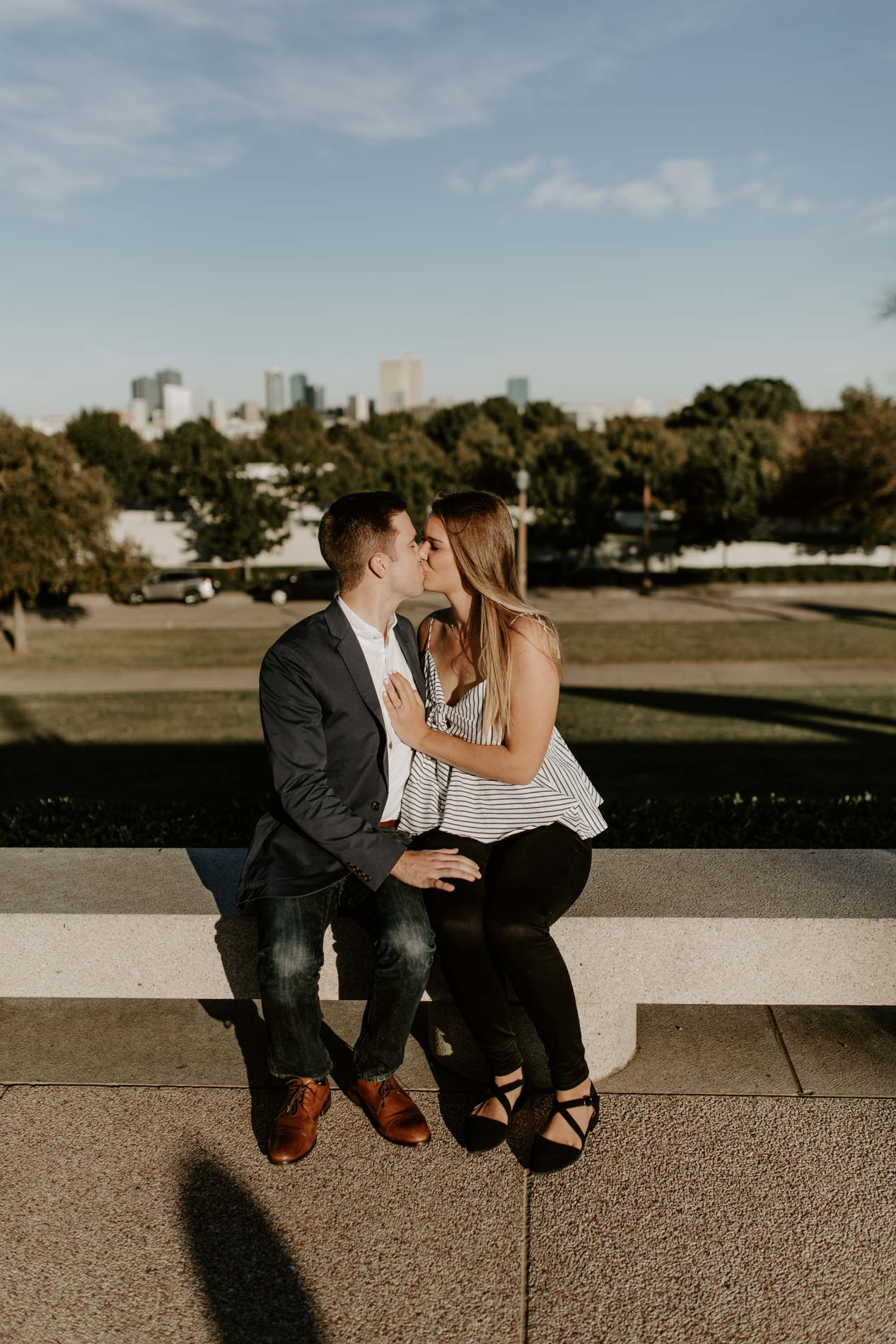 newly engaged couple kissing with a skyline view