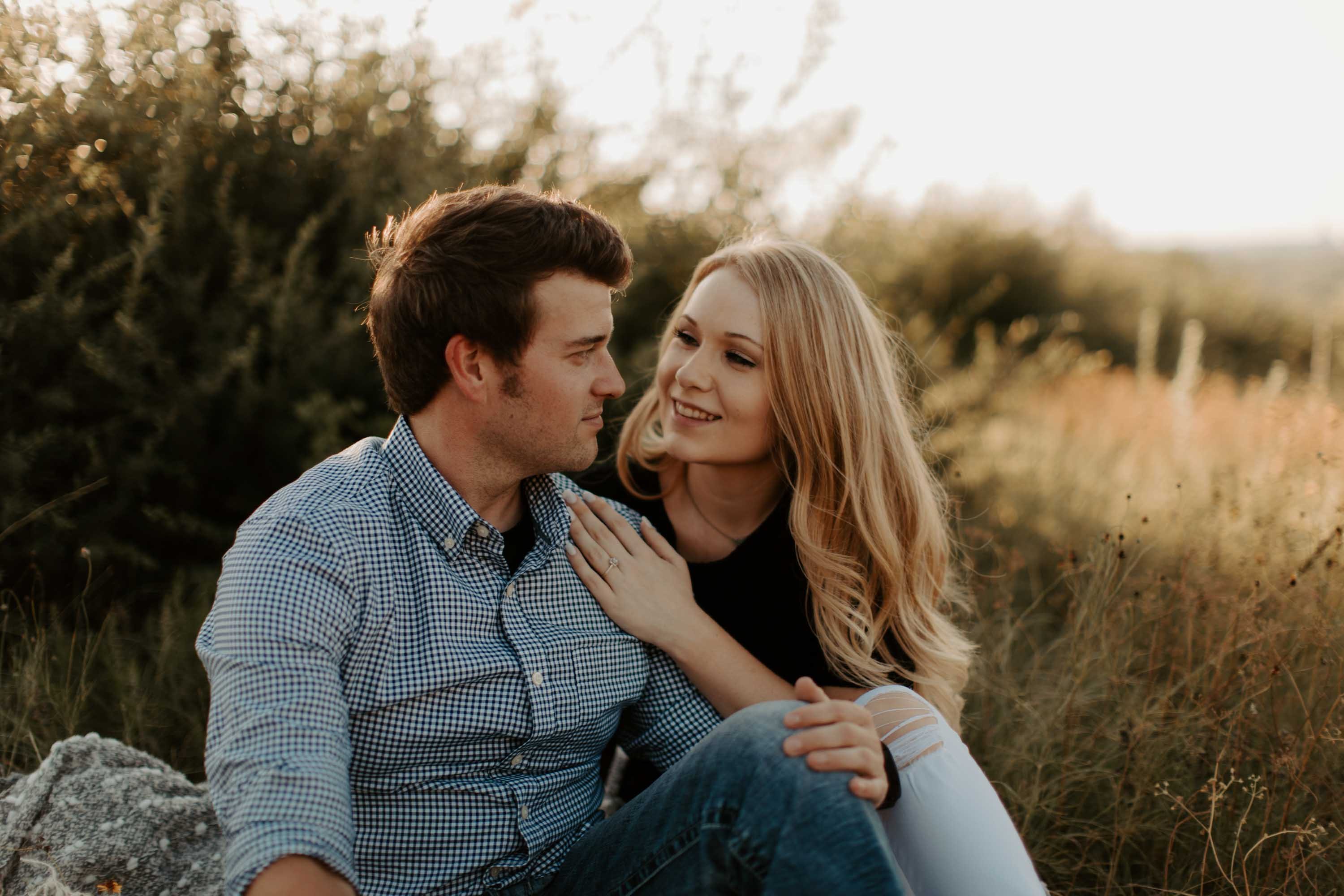 engaged couple sitting in Fort Worth at sunset