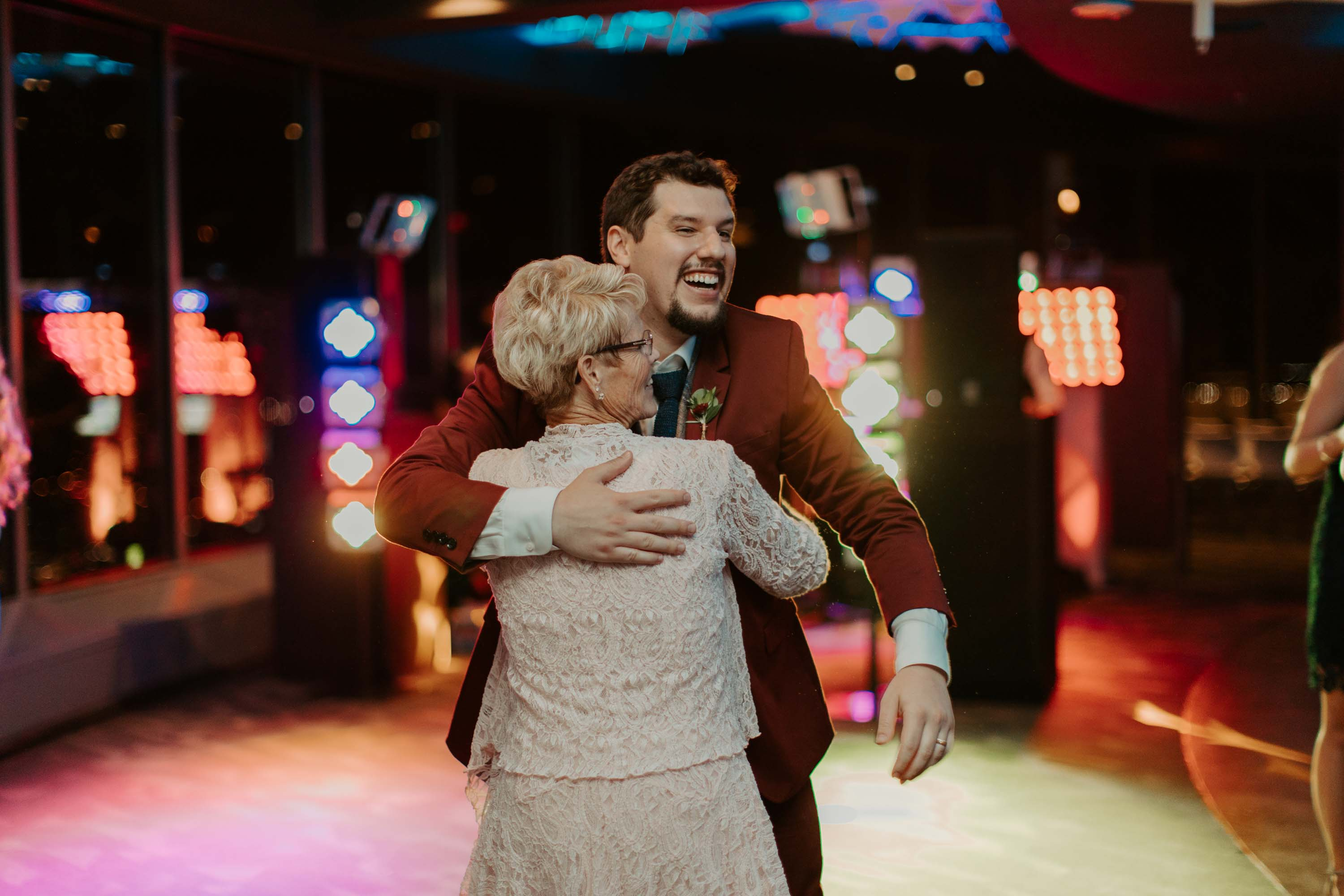 Groom dancing with family at wedding reception