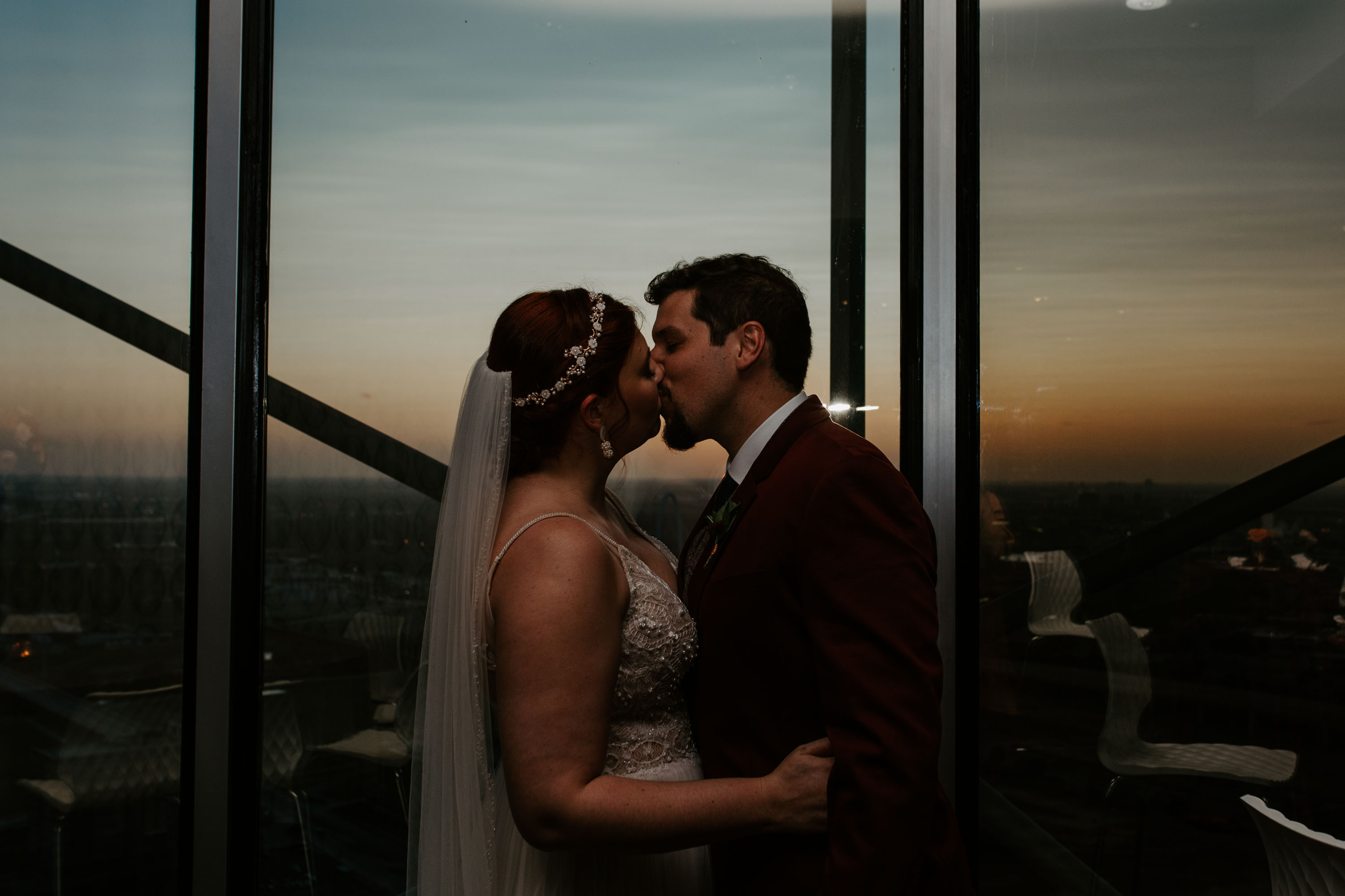 Bride and groom kiss at the end of their wedding reception in reunion tower in Dallas texas