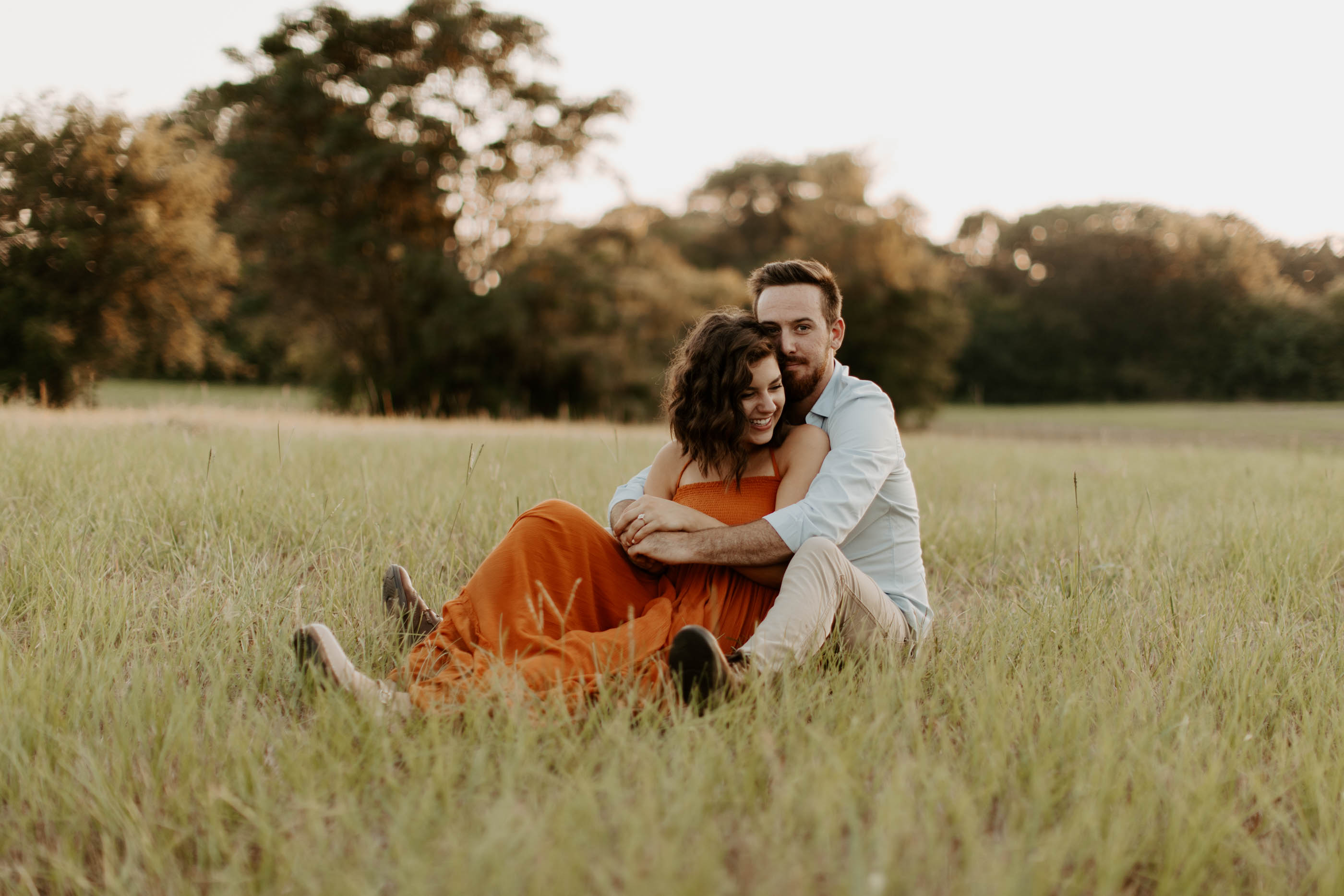 couple sitting in grass snuggling