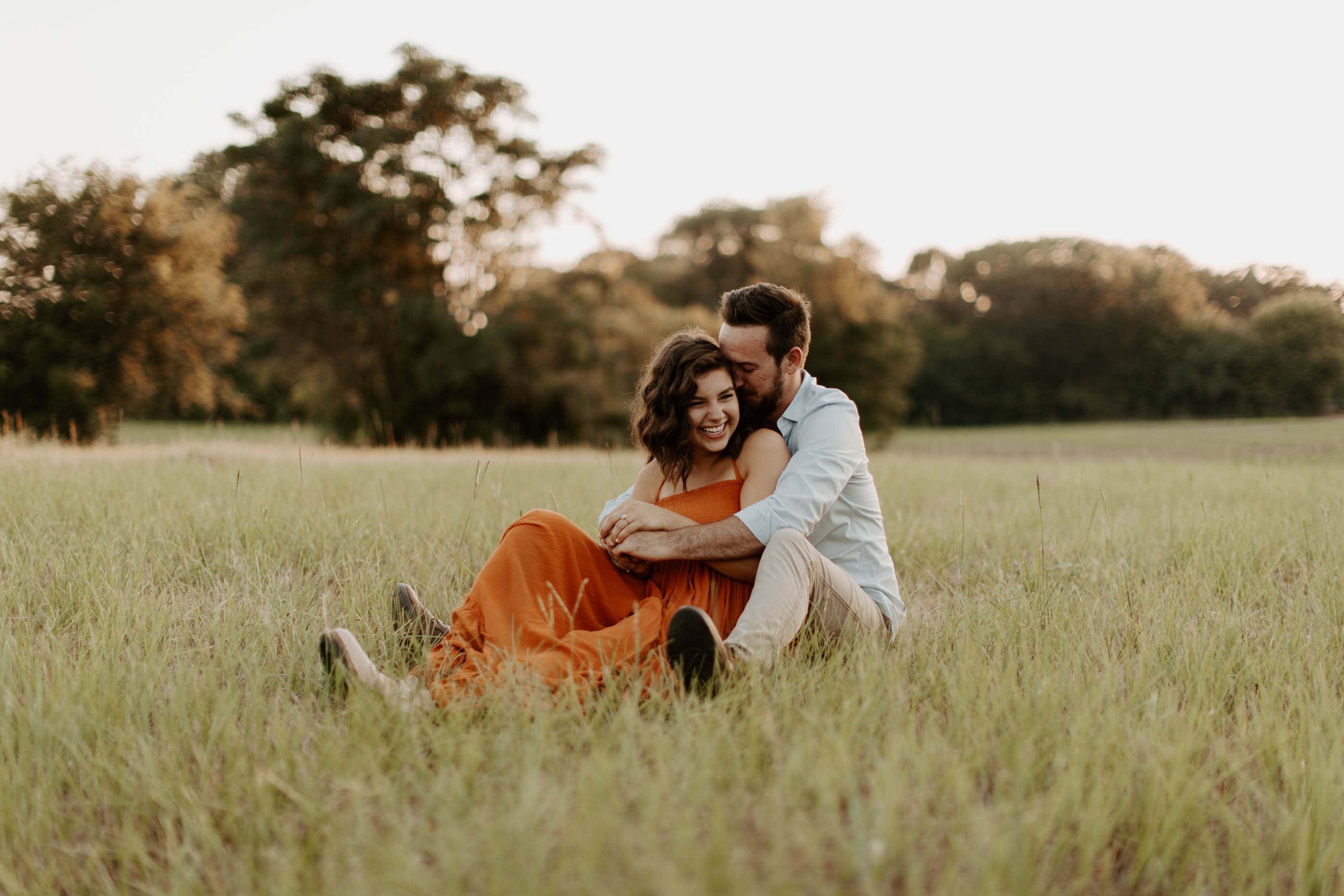 couple cuddling while sitting in grass at sunset