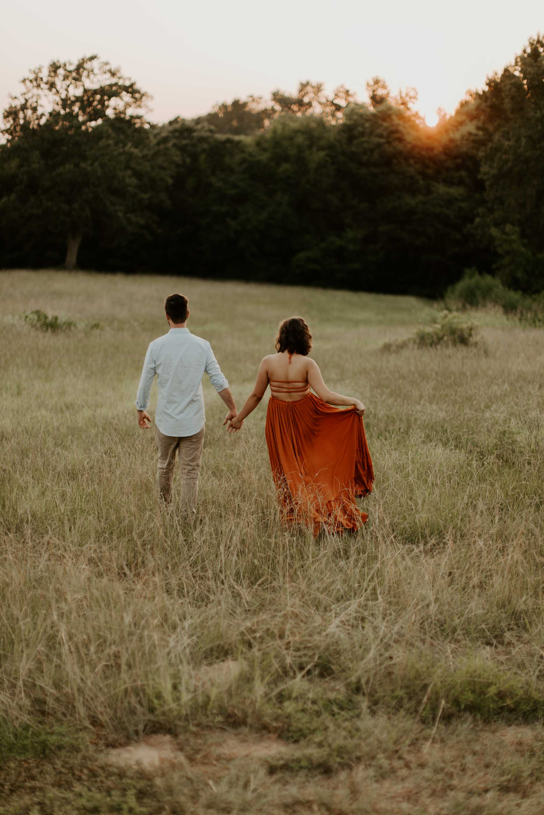 girl and boy holding hands and walking in field for engagement session
