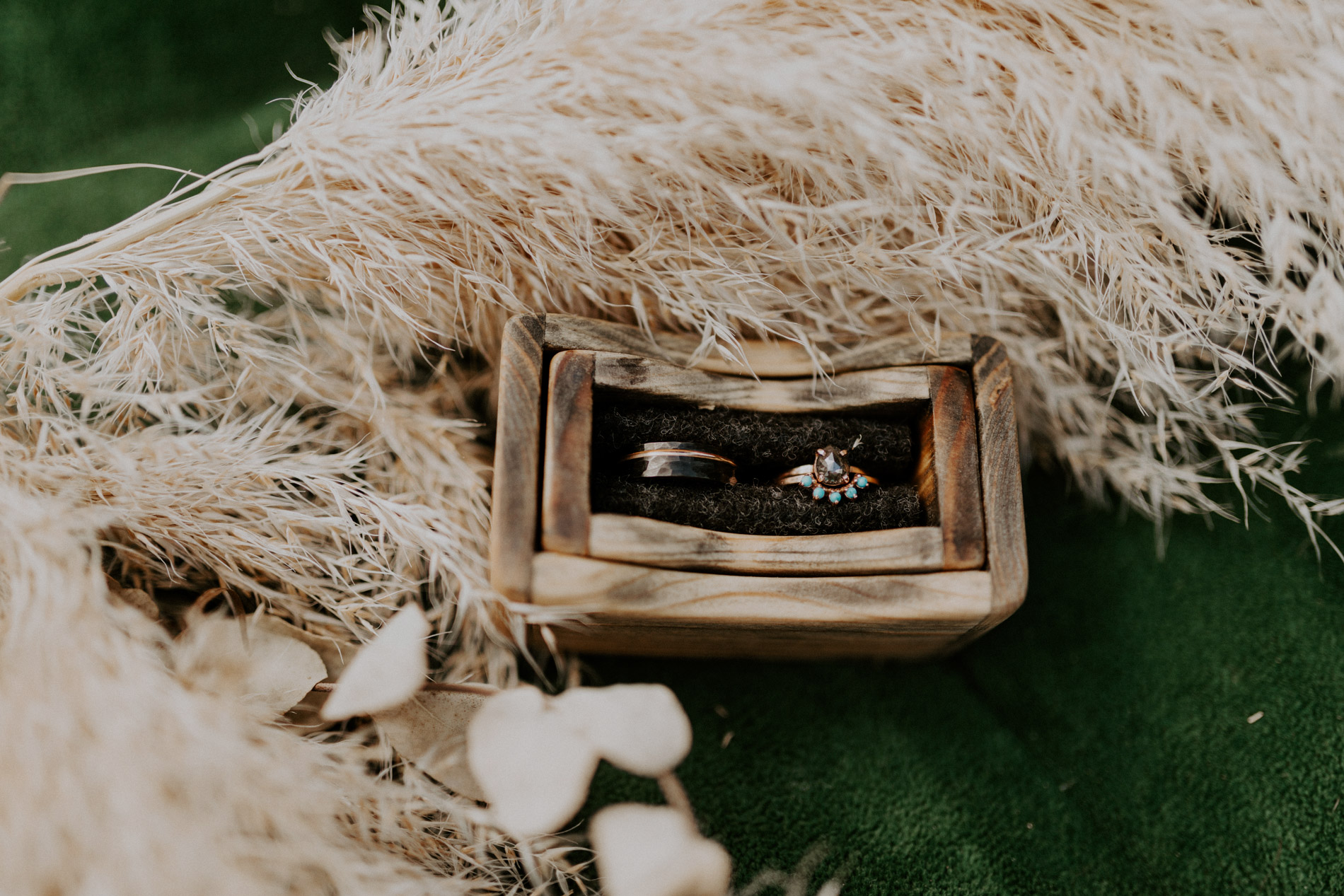 Bohemian wedding rings on green couch at East Texas wedding