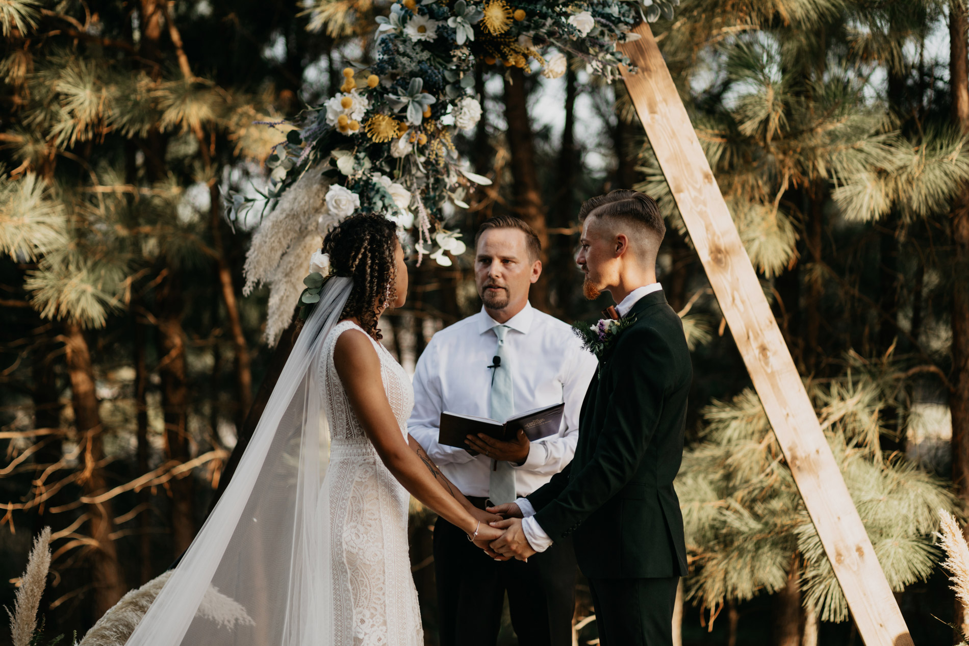 Bride and groom standing at the altar during bohemian wedding ceremony
