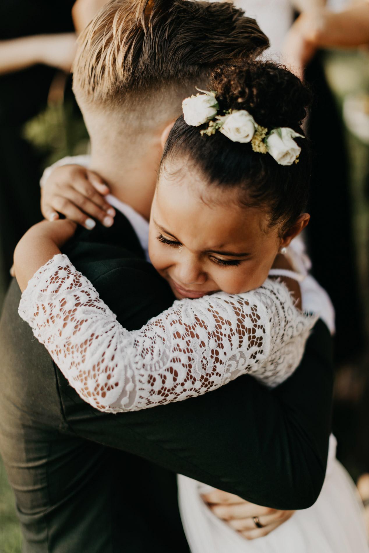 Brides little sister emotionally hugging the groom