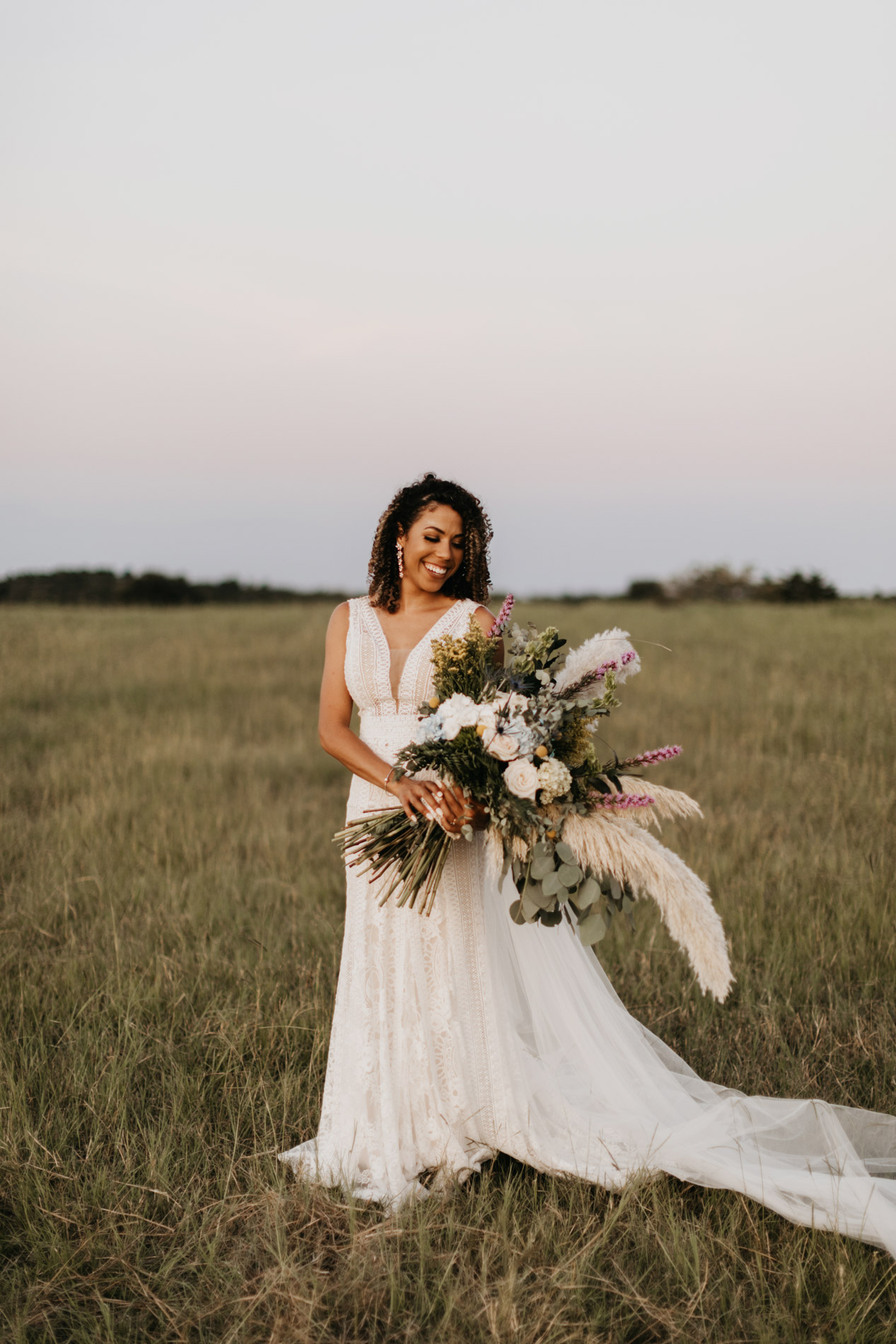 bride looking at her huge boho wedding bouquet