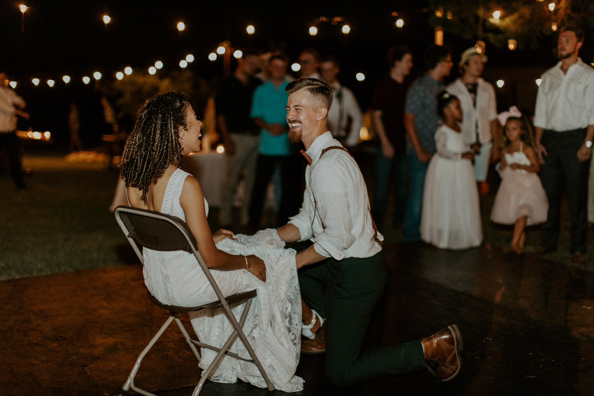 Bride and groom laughing during garter toss