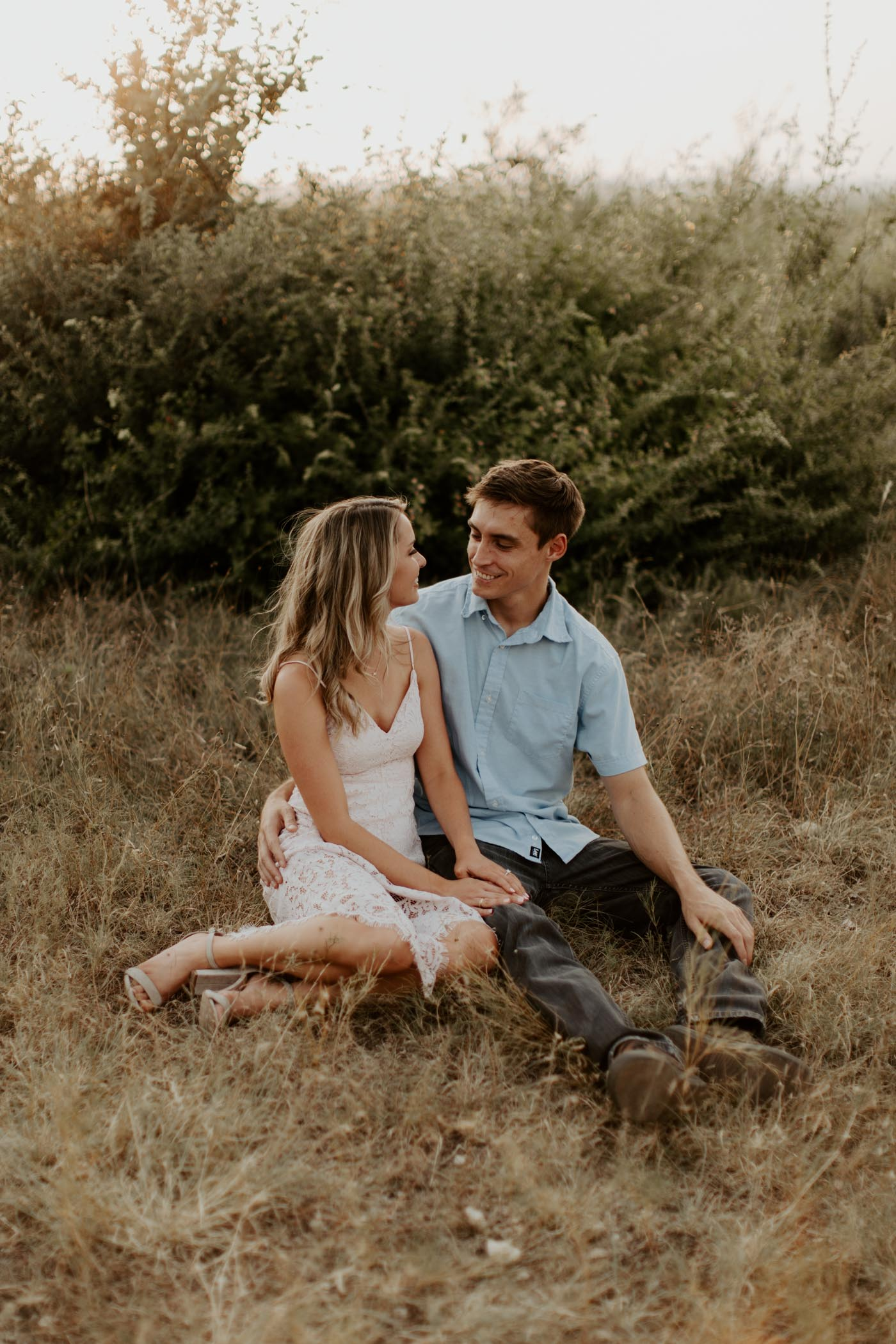 couple sitting in the grass during their engagement session