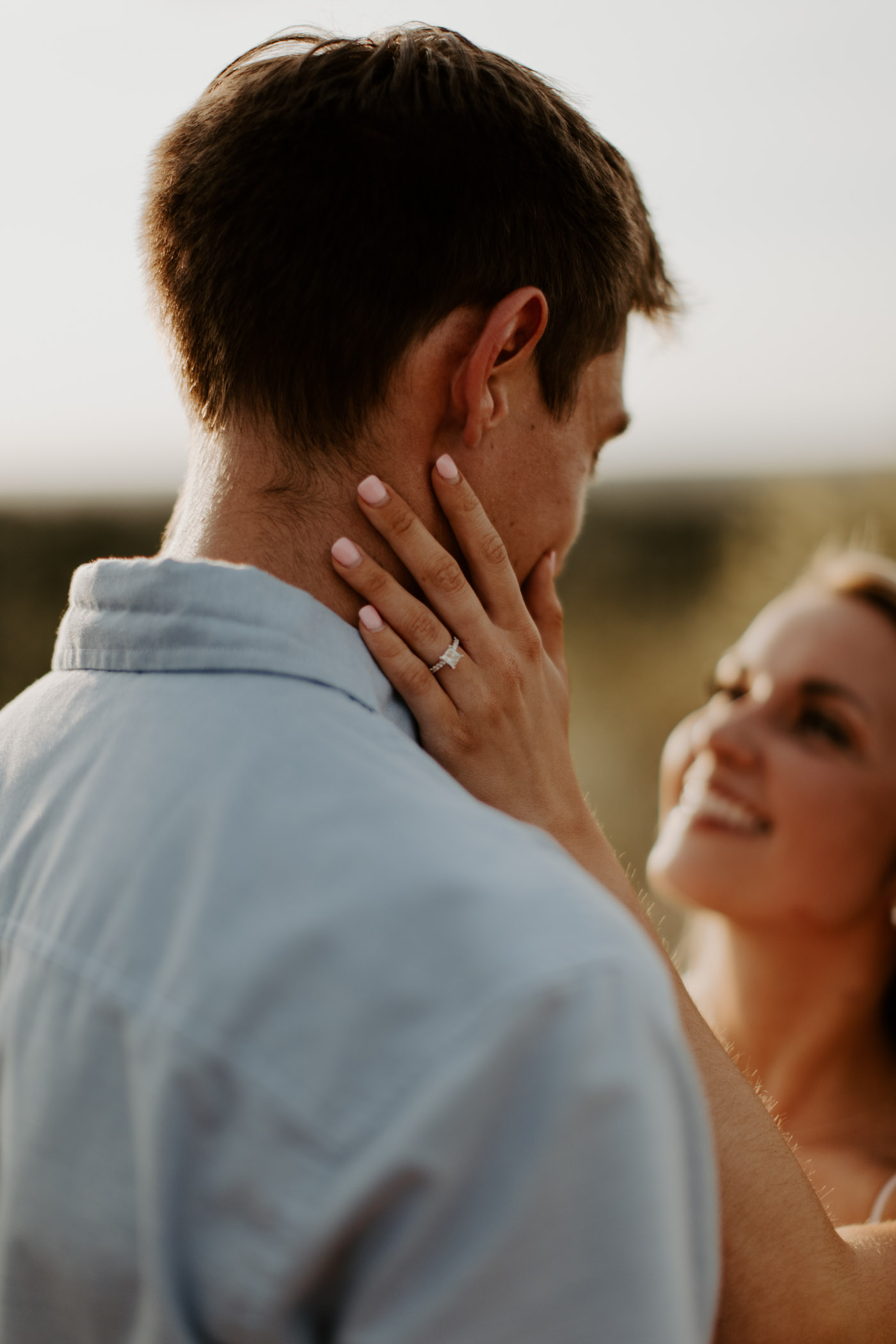 girl touching boys face with engagement ring on