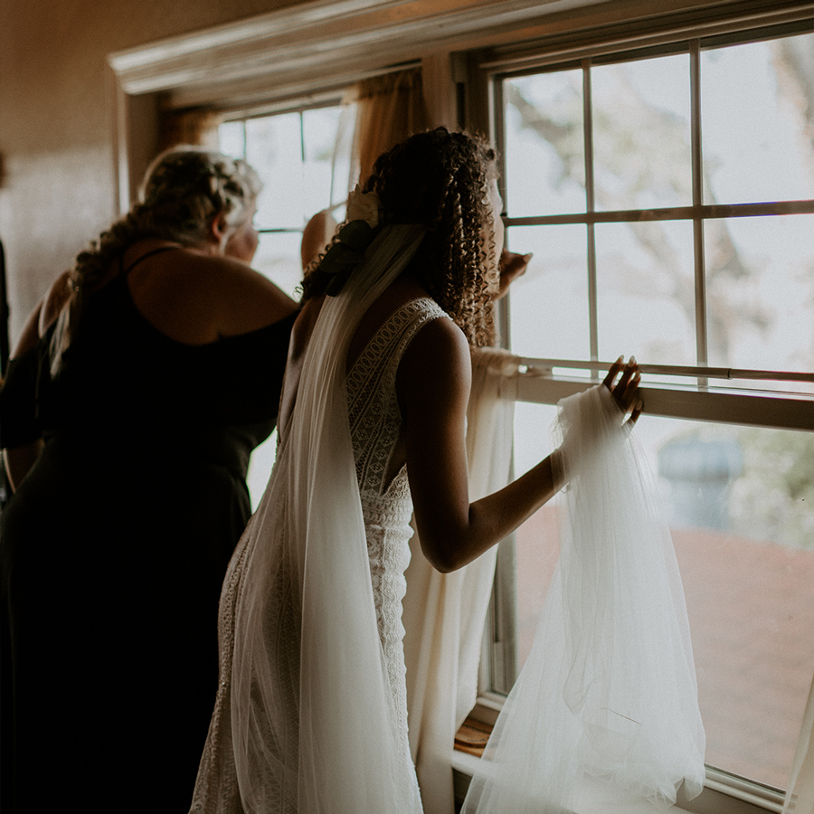 bride looking out window on wedding day
