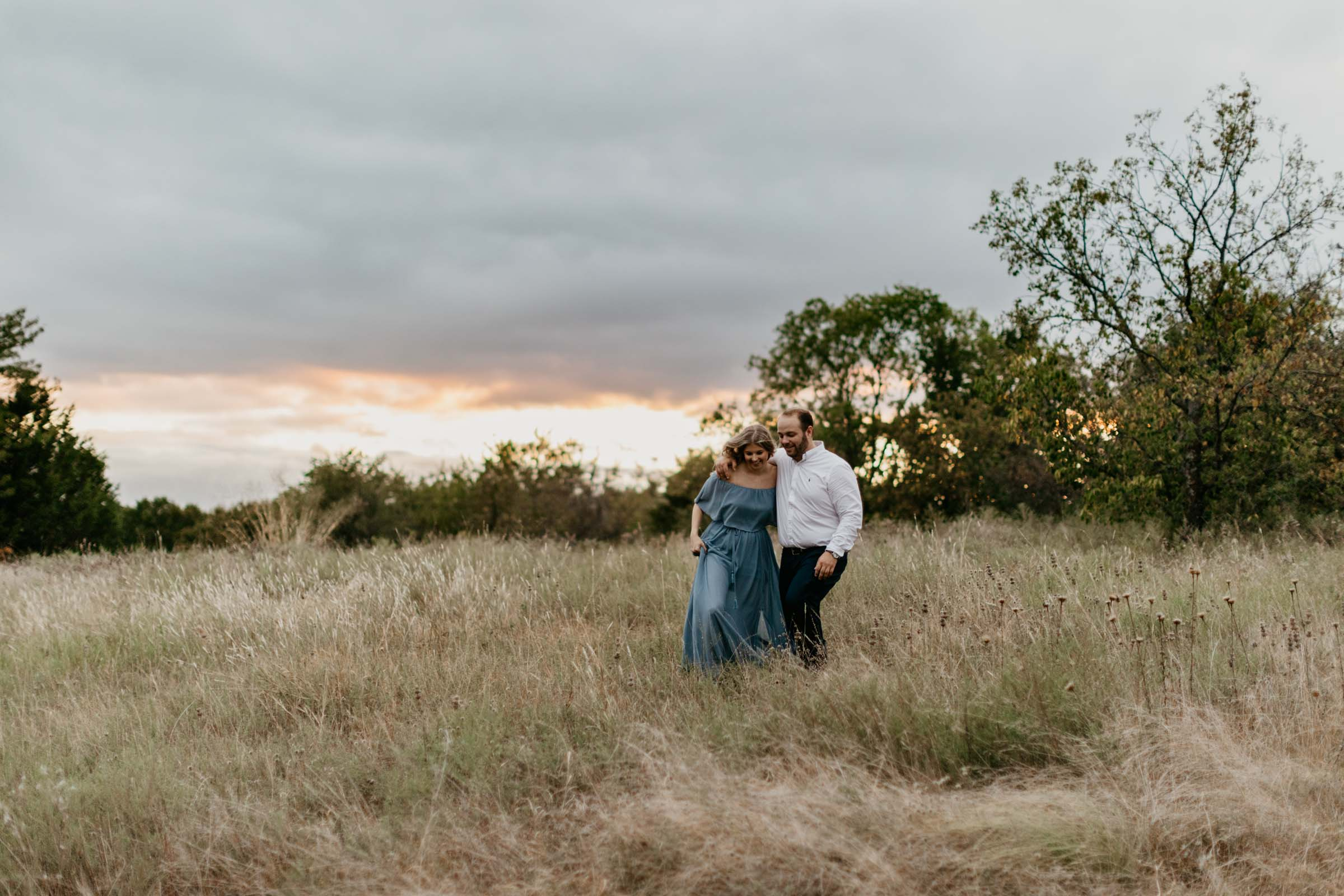Blue hour couple during fall for their engagement session walking in field