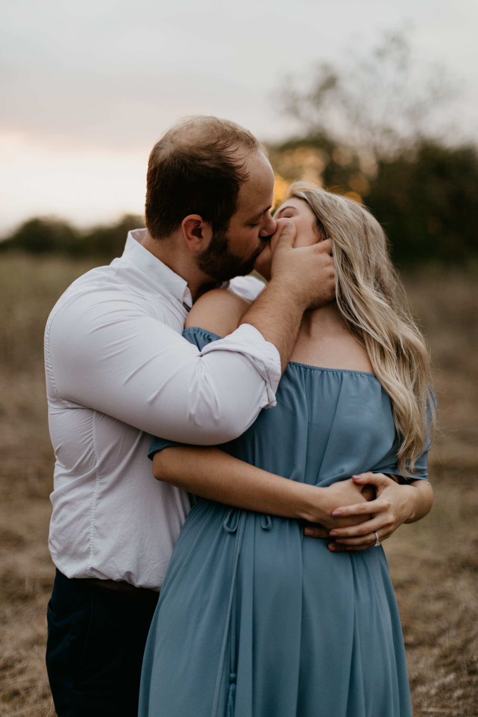 cute couple kissing romantically during their blue hour engagement session