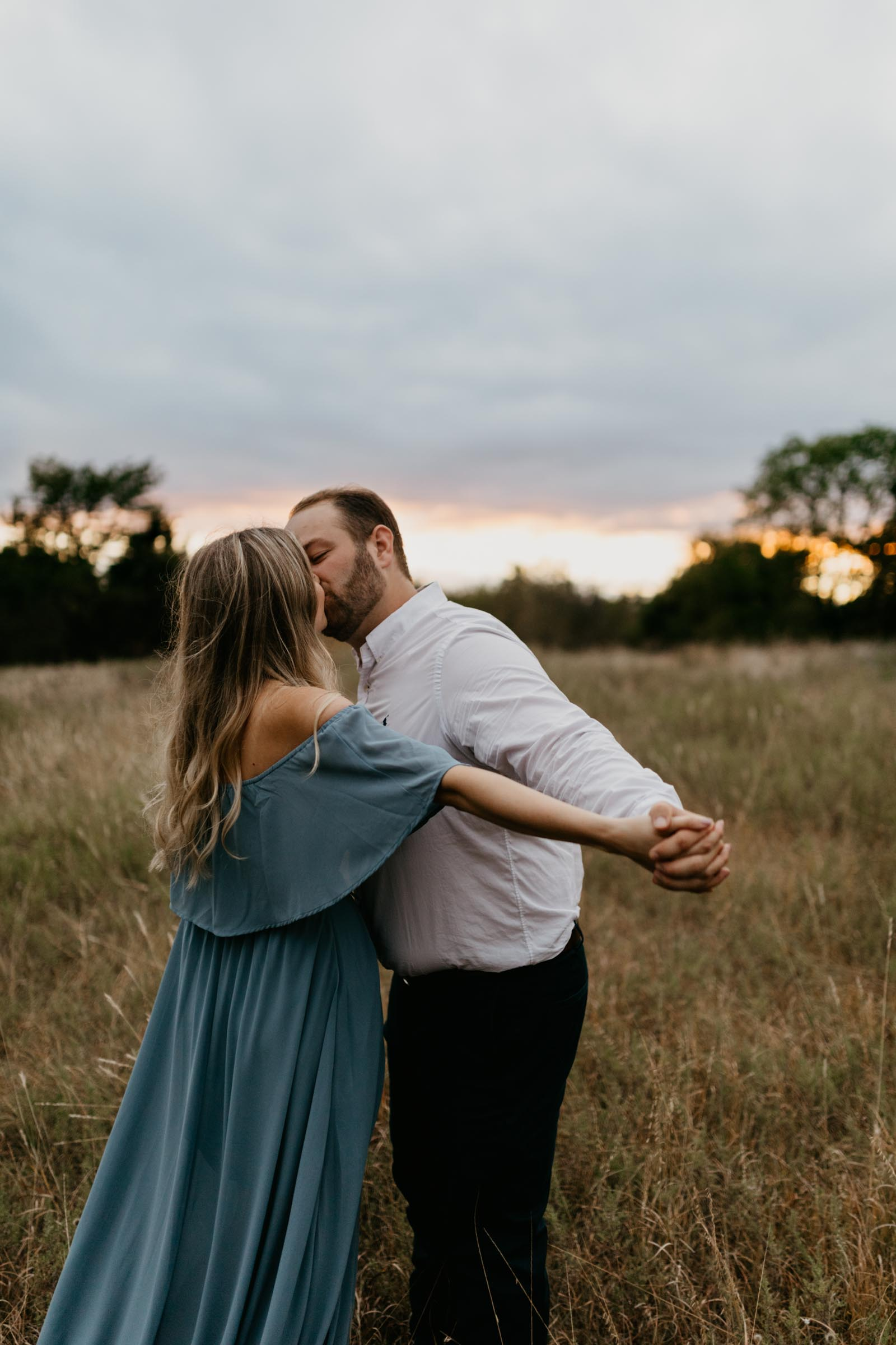 adorable couple kissing in a field during a photography session girl wearing blue dress