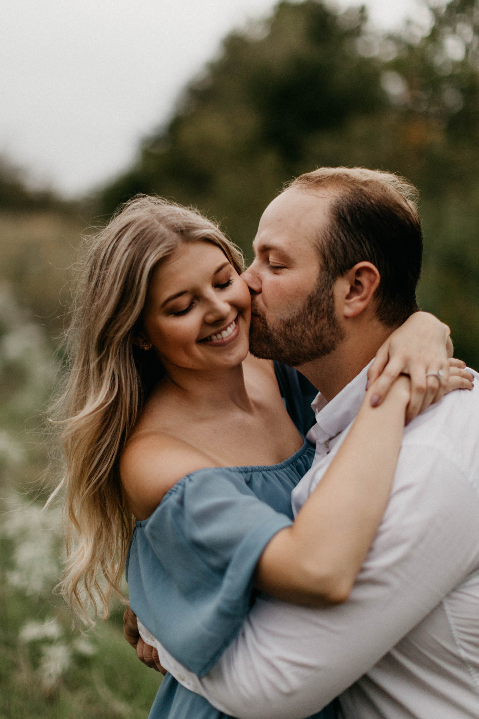 Boy kissing his fiancé on the cheek during their photography session