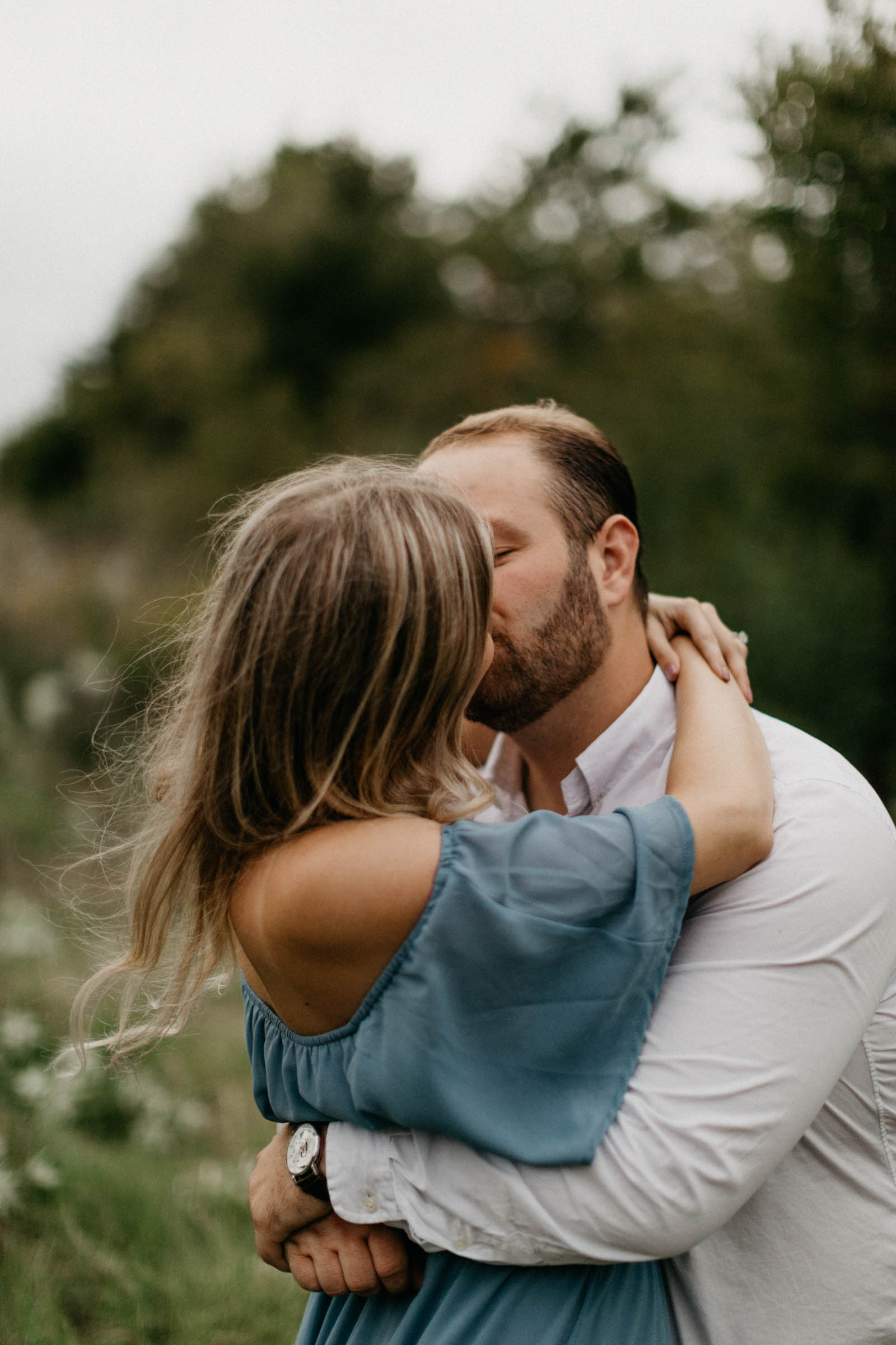 boy and girl making out during their photo shoot for engagement photos